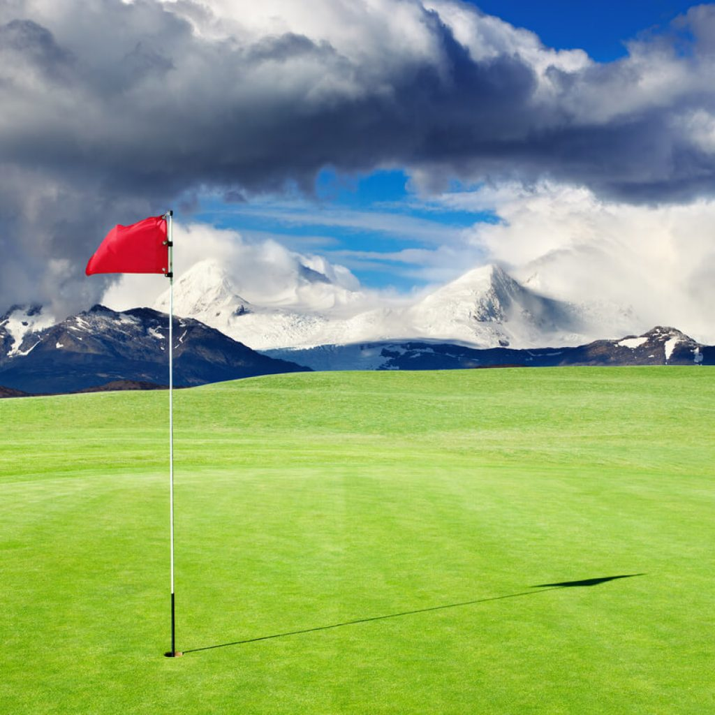 golf green with mountains in the background