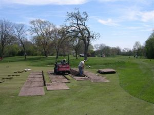 men installing drainage on green at Merion