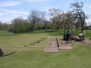 men working on the green at Merion
